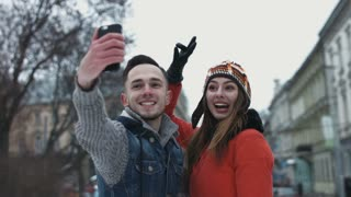 Sweet young couple making selfie on smartphone. Male and female in their 20s having a date outdoors and taking pictures by using mobile device. People make faces on camera.