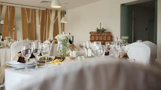 Table set in white decoration for wedding or another catered event dinner.