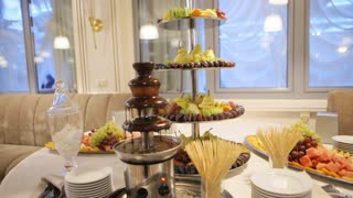 Tasty chocolate fountain and a lot of sweet desserts prepared in a good restaurant for wedding party.