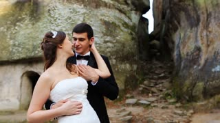 The bride and groom are hugging each other in nature. The couple are standing in front of rocks