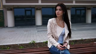 Thoughtful young brunette woman sitting on a bench in city and listening to music or a podcast on a smartphone.