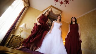 Three beautiful women jumping on the bed and having fun before wedding ceremony started.