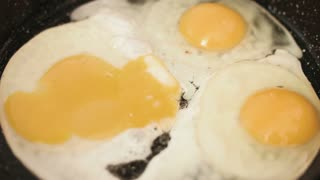 Three fried eggs preparing  on a cast-iron frying pan and treated with a salt.