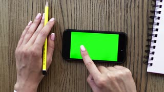 Top view of female hand with smart phone, notebook and pencil over wooden table background.