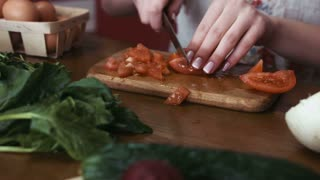 Tracking footage of a female hands with french nails are cutting a tomato to slices for making a salad, greenery and vegetables lie on a table
