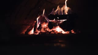 traditional wood fire pizza oven with flames in slow motion