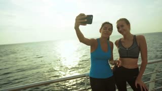 Two beautiful active ladies taking pictures after morning jogging.