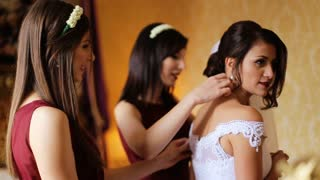 Two beautiful bridesmaids wearing same cherry dresses preparing a bride for a weddding ceremony at her home.