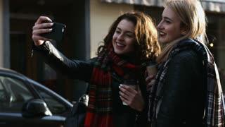 Two best friends taking selfies on the street.