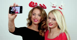Two models with christmas accessories in their heads make selfie pictures by using smartphone; girls having funny faces on camera