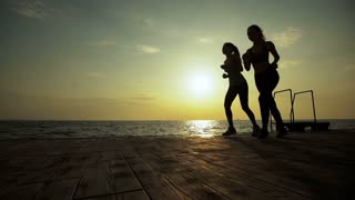 Two slim active ladies running in the evening time.