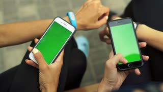 Two sportswomen sitting on a bench, holding two smartphones in hands. Green screen Chroma Key. Close up.