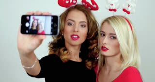 Two women are taking pictures on a smartphone camera; girls make selfies in studio during photosession.
