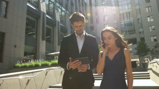 Two young colleagues walking on stairs, woman talking on phone, man using tablet outdoors.