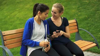 Two young girls sitting on a bench, one girl holding smartphone, other one vacuum bottle.