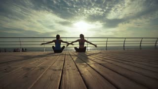 Two young ladies sitting in lotus pose and meditate near the sea.