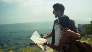 Two young people wearing sunglasses holding a map and planning new destinations.