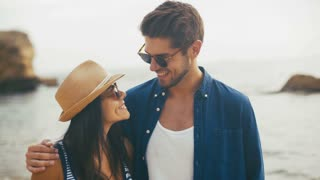 Two young smiling people in funny sunglasses posing on the beach.