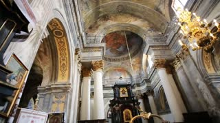 Vertical panorama shot. View of the benches, vintage ceiling, interior, statues, frescoes, old organ