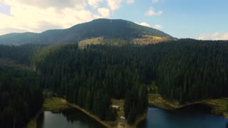 Aerial drone footage of lake and mountains against sky. Fast tracking shot of rippled water and on lake. Reflection of clouds is falling in water.
