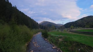 Aerial view. beautiful view from above. View of mountain river near the forest. Blue clouds. Flying over the river and green fields