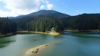 Aerial view. View from above. View of mountain lake near the forest. Blue clouds. Flying over the lake and green fields