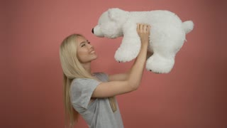 Attractive positive blonde hugging white teddy bear on pink background