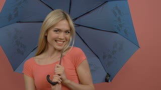 Attractive smiling caucasian blonde woman playing with blue umbrella on pink background