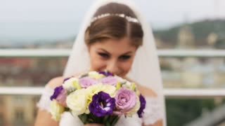 Beautiful bride smelling wedding flower bouquet, spinning round and looking at the camera in blurred old city background. Close up