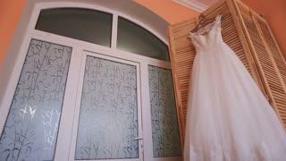 Beautiful elegant long wedding dress on hanger on wooden background. Wedding preparation