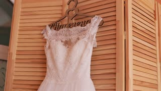 Beautiful luxurious wedding dress on hanger on wooden background. Wedding preparation