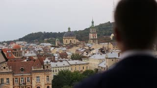 Blurred grooms back. Groom looking at the city landscape. Lviv. Ukraine. Landscape view of the city from above. Beautiful old city buildings. Antique