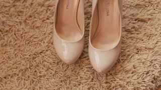 Bridal wedding shoes. Close up view of woman's nude highheels on the carpet.