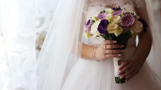 Bride holding wedding bouquet. Beautiful wedding flower bouquet in brides hands. Close up. Yellow, pink and purple bridal bouquet.