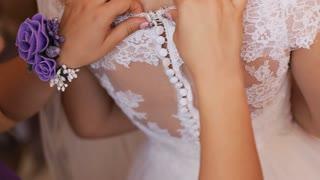 Bridesmaids hands buttoning up beautiful bride wedding dress. Close up