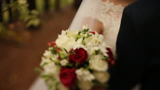Close up bride holding beautiful wedding bouquet with red and white roses. Fresh wedding flower bouquet. Bridal bouquet
