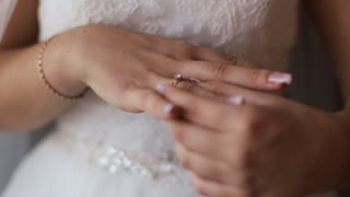 Close up brides correcting wedding ring on her hand.