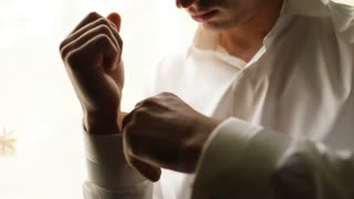 Close up man dressing white shirt. Groom hands buttoning sleeves before ceremony. Mens fashion. Businessman buttoning white shirt sleeves