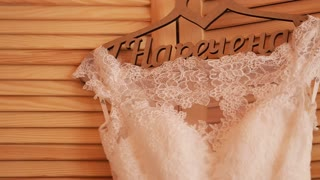Close up of a beautiful luxurious wedding dress on hanger on wooden background. Wedding preparation