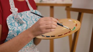 Close up of creative painter holding wooden palette on her hands and making beautiful colors in studio.