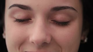 Close up of young woman opening her eyes and blinking. Close up green eye. Slow motion. Girl smiling and opening her eyes