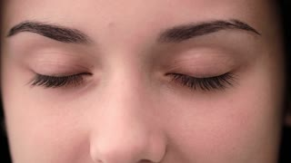 Close up of young woman opening her eyes and blinking. Close up green eyes. Slow motion