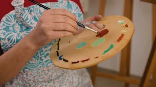 Close up portrait of woman`s hand mixing paint on palette at workshop.