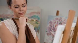 Close up portrait of young talented painter working in her art studio.