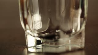 Close up shot of filling up empty glass with water. Slow motion. Bubbles go up. Close up view of glass bottom