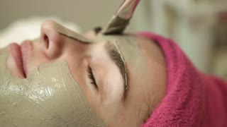 Close up view of face. Professional master applying clay on womans face in spa salon. Face care in beauty salon. Treatment