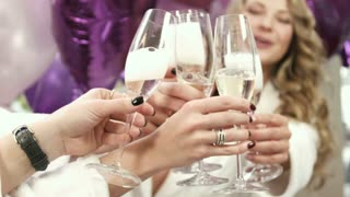 Close up view of girls opening champagne bottle. Drinking champagne at the party.