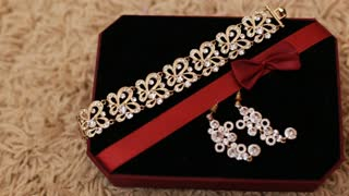 Close up view of golden bracelet and earrings with diamonds in jewelry box. Beautiful luxurious jewelery in gift box with black cloth.