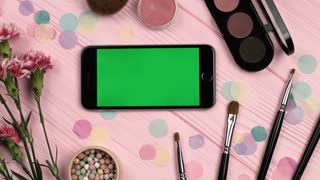 Close up view of horizontal mobile phone with green screen on pink wooden table with make up brushes, lipstick, flowers, eyeshadows. View from above. Make-up theme. Chroma key