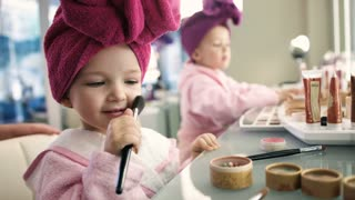 Close up view of pretty little girl in pink robe doing herself make up in salon